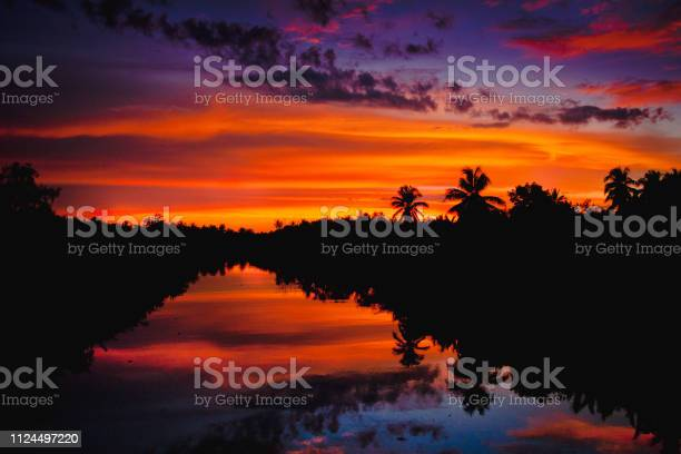 Photo of colorful sunset with clouds light rays over the river with reflections on silhouette nature landscape background