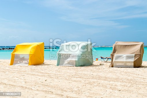This tranquil beach scene was taken in Aruba.  The beach features white, sugary sand in the foreground and the turquoise Caribbean sea in the background.  Colorful sunshades on the beach set the welcoming scene.  Peaking out from behind the shades the limbs of a sunbather can be seen.