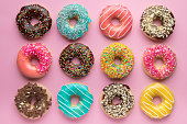 Colorful sweet background. Delicious glazed donuts on pink background