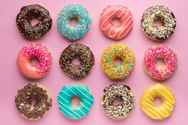 colorido fondo dulce. deliciosas rosquillas acristaladas sobre fondo rosa. - postre fotografías e imágenes de stock