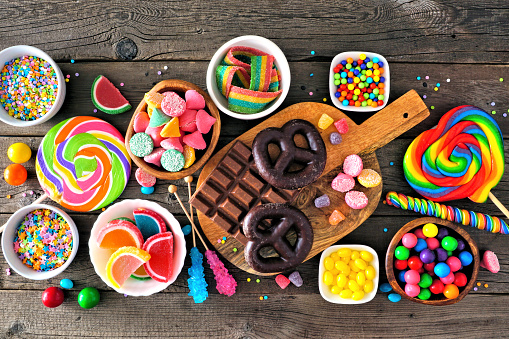 Colorful sweet candy buffet table scene. Above view over a rustic wood background.