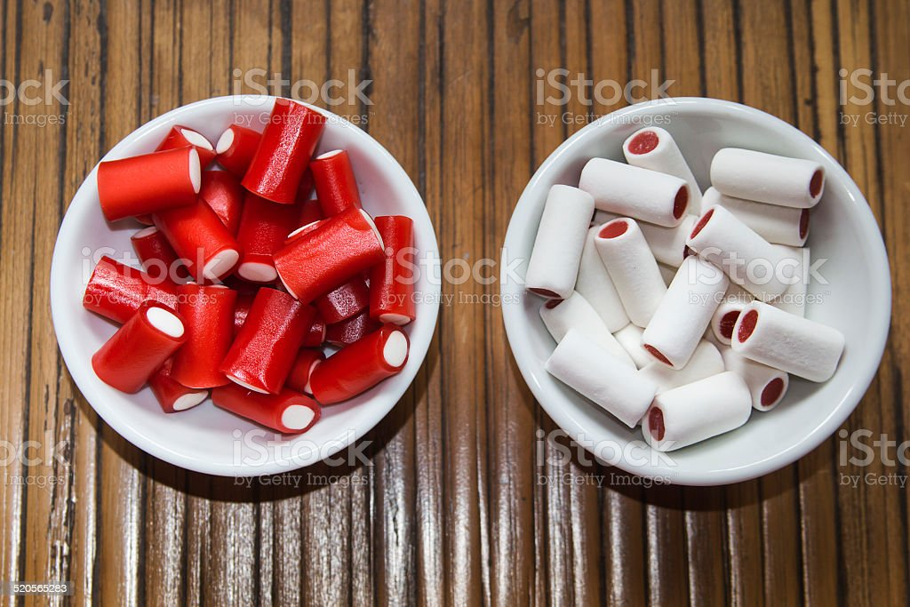 Colorful sweet in a white bowl over wooden table stock photo