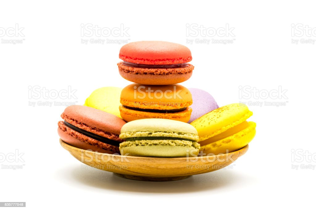 Colorful sweet macarons in wooden plate stock photo