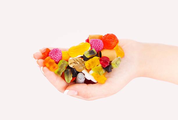 bunten süßigkeiten in frau hand mix - haribo lakritz stock-fotos und bilder