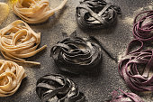Colorful raw pasta on black background. Italian tagliatelli nests with natural colorings