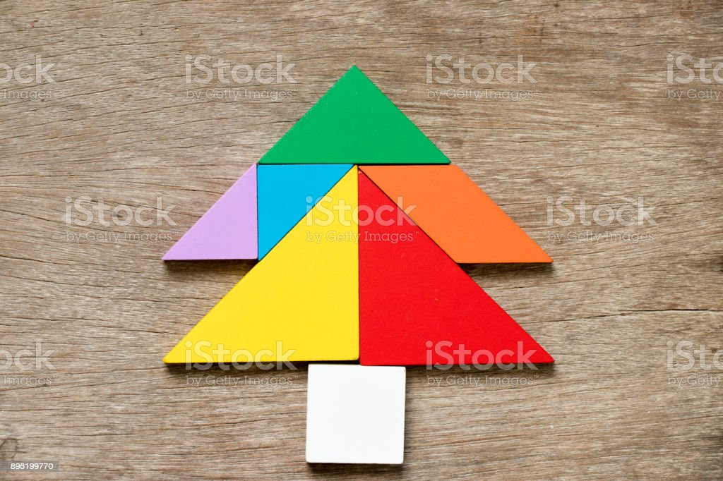 Colorful tangram puzzle in Pine or christmas tree shape on wood background stock photo
