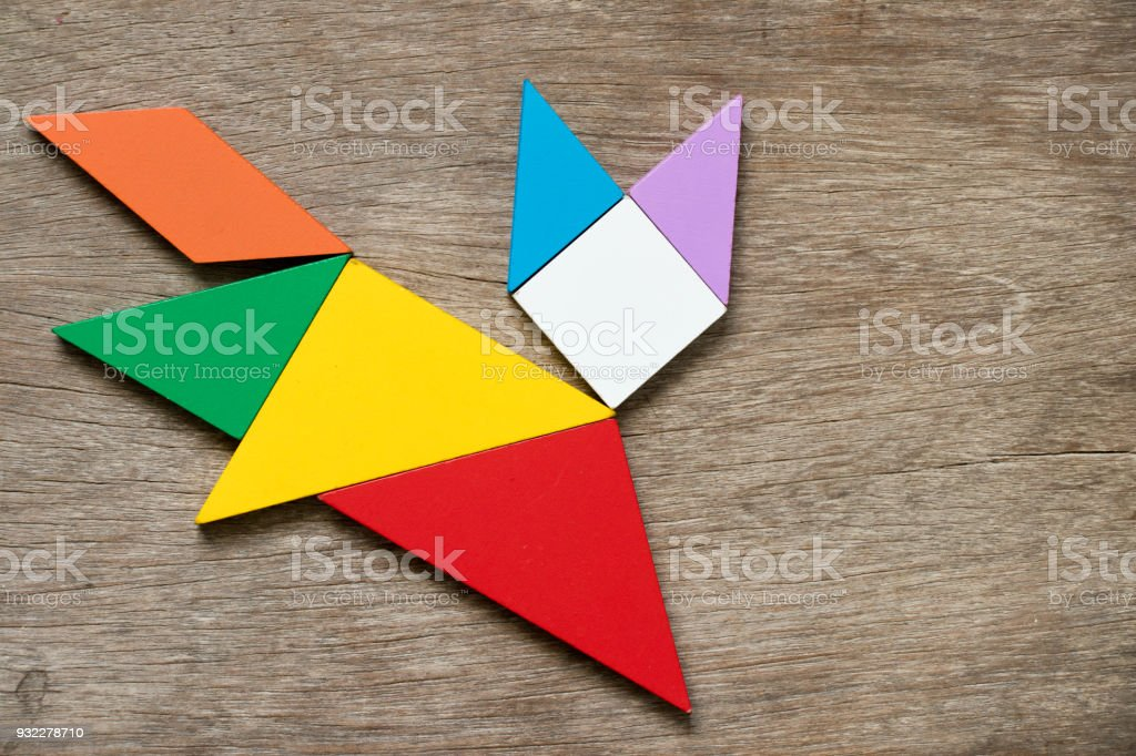 Colorful tangram puzzle in running cat or fox shape on wood background stock photo