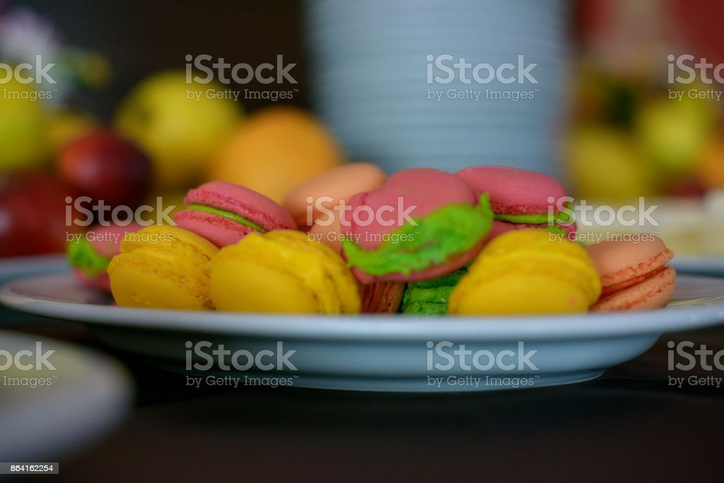 Colorful, tasty French macarons on a white plate at a dessert bar royalty-free stock photo