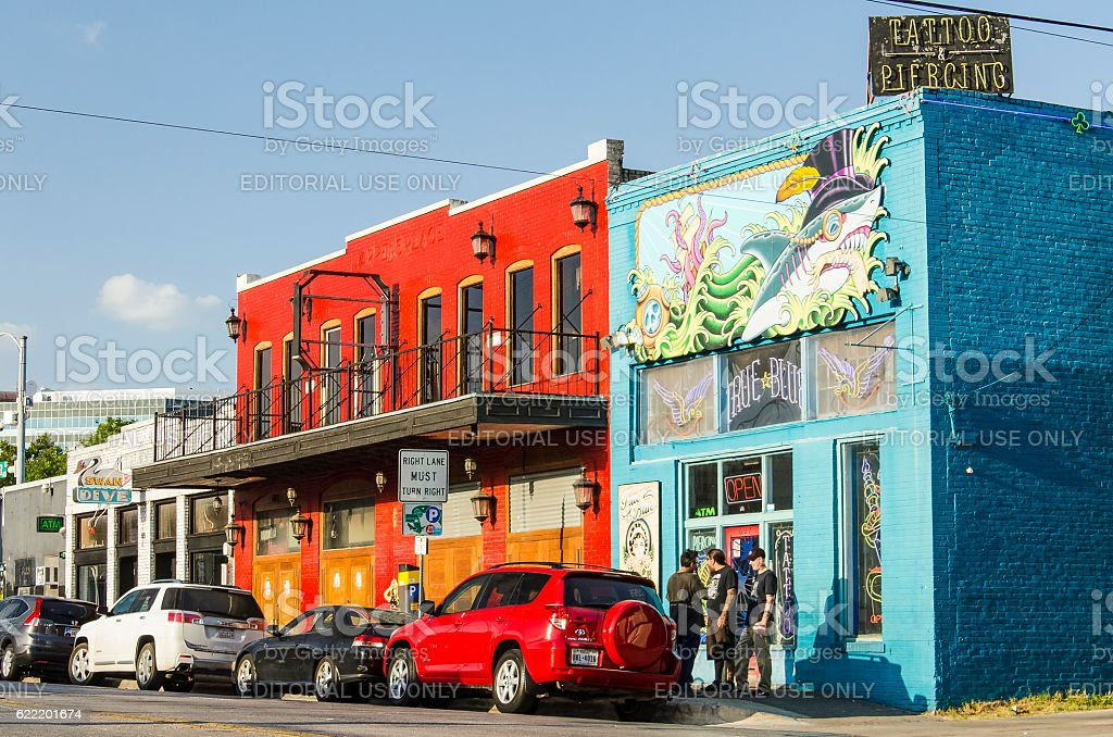 Colorful tattoo and piercing store buildings on street in downtown stock photo