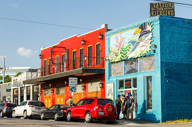 Colorful tattoo and piercing store buildings on street in downtown – Foto