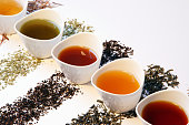 small porcelain tea pots with different sorts of tea such as black tea, matcha tea, gunpowder tea, green tea, rooibos tea