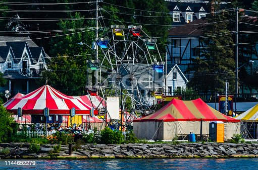 Colorful tents and ferris wheel of a small waterfront carnival