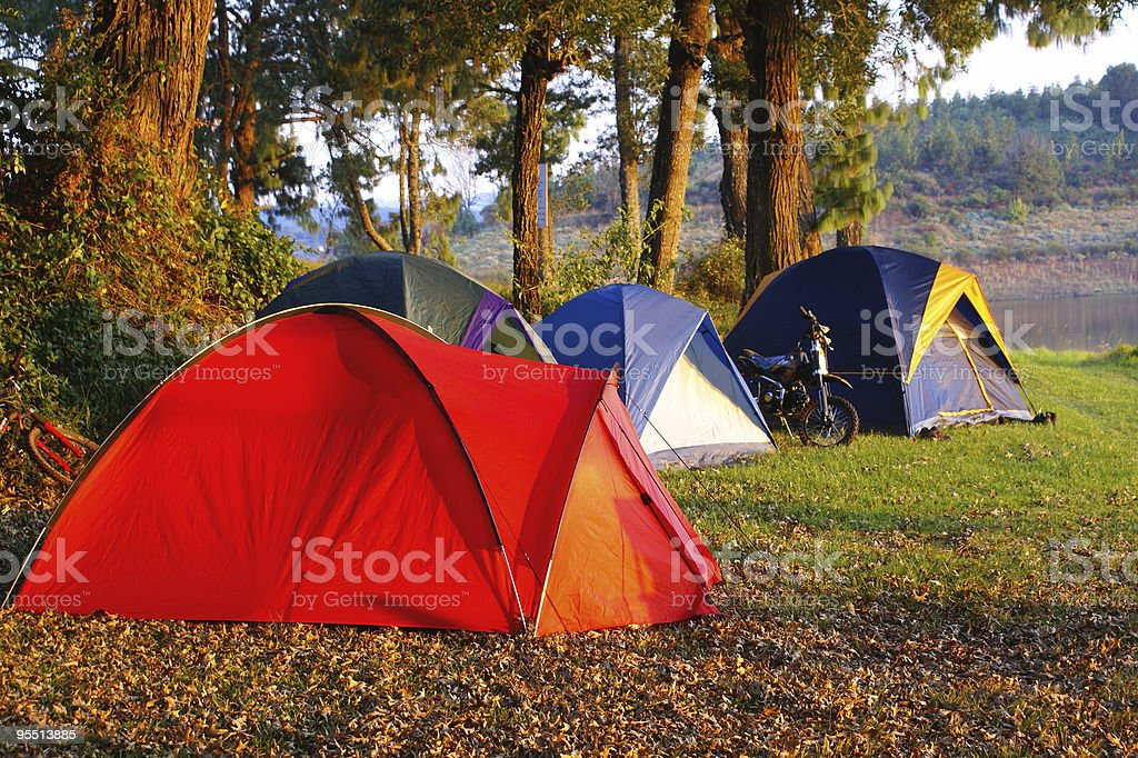 Colorful tents on camping site at sunset stock photo