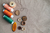 Colorful thread spools used in textile industry and buttons with a needle