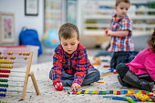 A multi-ethnic group of young children are indoors in a preschool. They are wearing casual clothing. In the foreground, a Caucasian boy is lining up colorful wooden tiles.