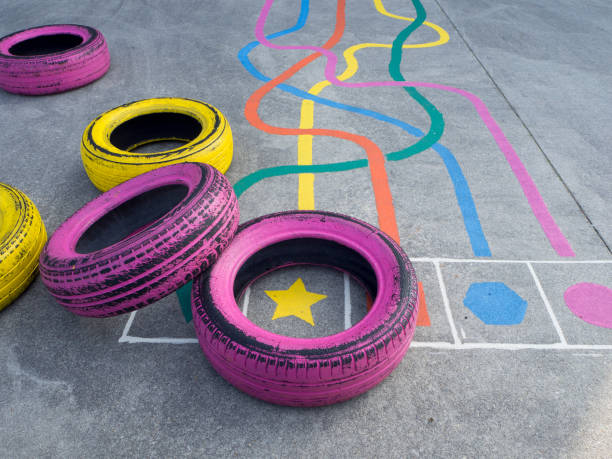 Colorful tires and games in a playground Colorful tires and games in a playground in a school yard, tire recycling obstacle course stock pictures, royalty-free photos & images