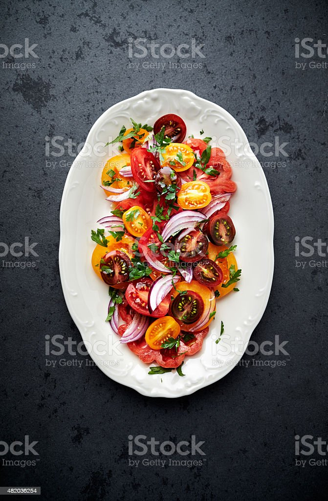 Colorful tomato salad with fresh parsley stock photo