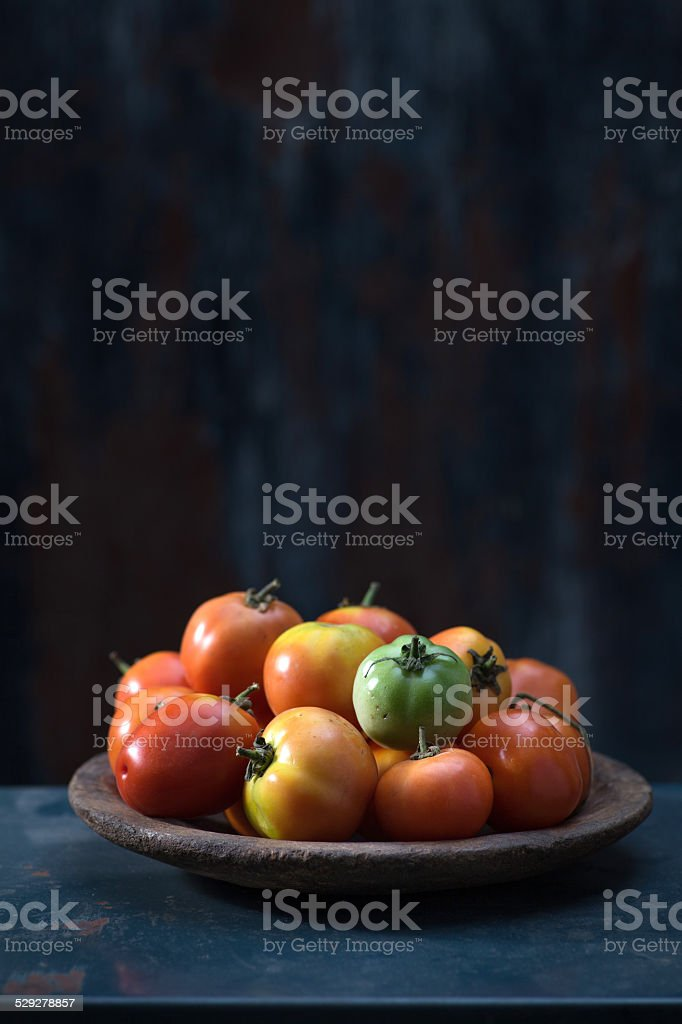 Colorful tomatoes on dark wooden background stock photo