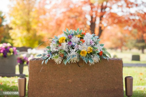 A colorful spray of flowers grace the top of a tombstone in the fall.
