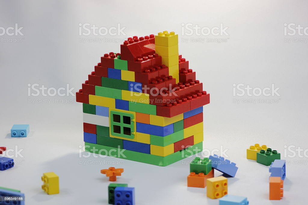 Colorful toy house with bricks in mess stock photo