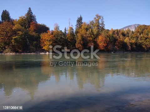 colorful trees at riverban with mountain panorama in autumn, Wörgl, Austria