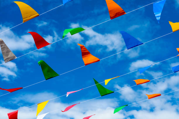 colorful triangular flag line moving by wind on blue sky white cloud background stock photo