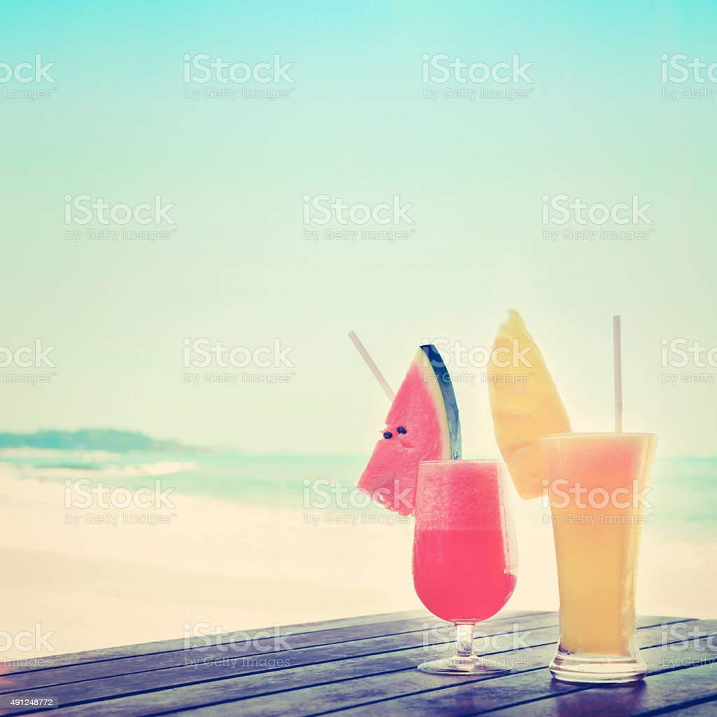 Colorful tropical fruit smoothies on wood table at the beach stock photo