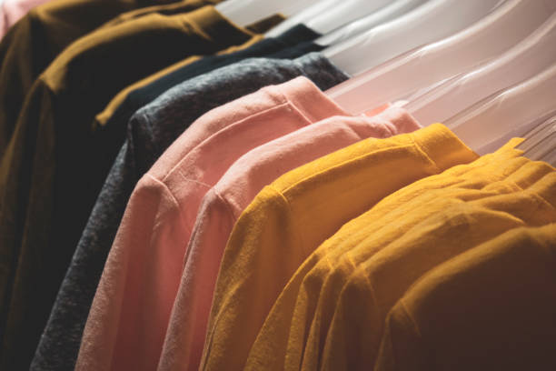 Colorful t-shirts on a hanger in fashion store stock photo