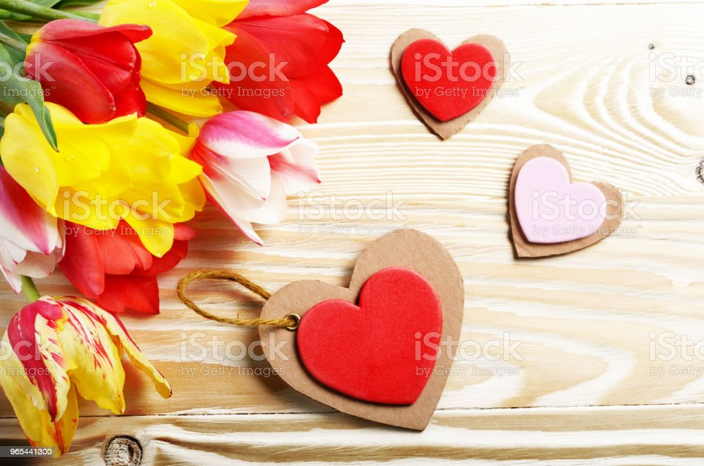 Colorful tulip flowers and heart shape cards on wooden table background with space for text royalty-free stock photo