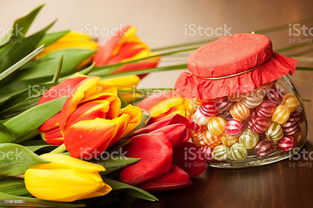Colorful tulips and candies on a wooden surface royalty-free stock photo