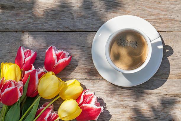colorful tulips and coffee cup on garden table - meerdere lagen effect stockfoto's en -beelden