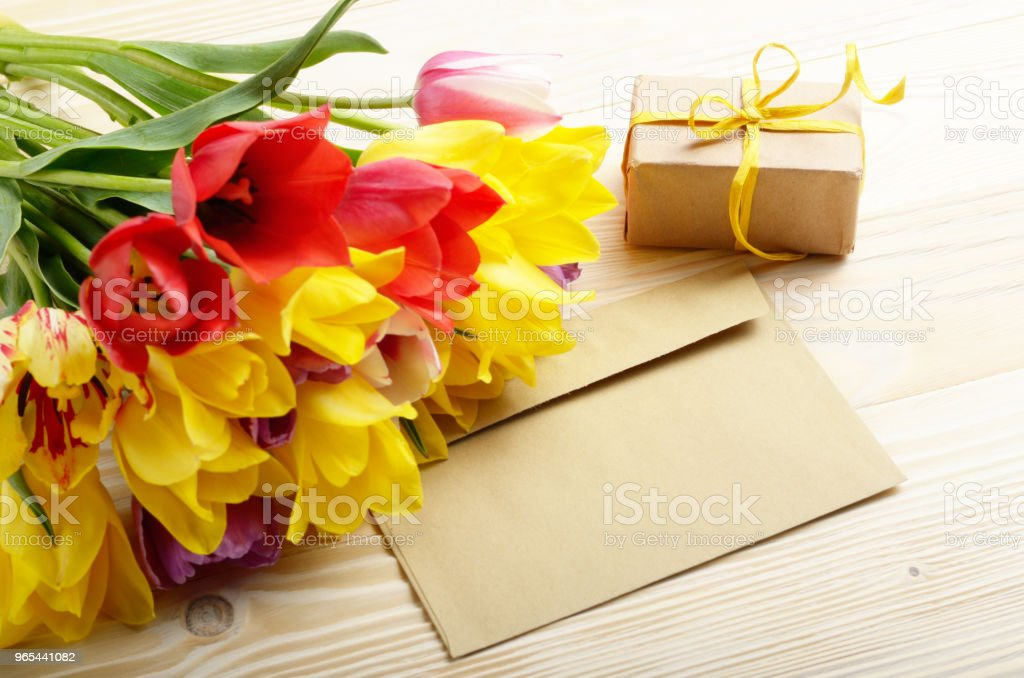 Colorful tulips blank envelope and gift box on natural wooden background with space for text zbiór zdjęć royalty-free