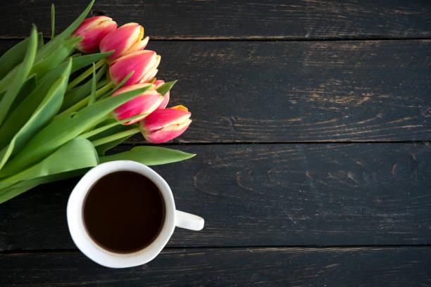 bunte tulpen strauß und kaffeetasse  - tropfenblatt tisch stock-fotos und bilder