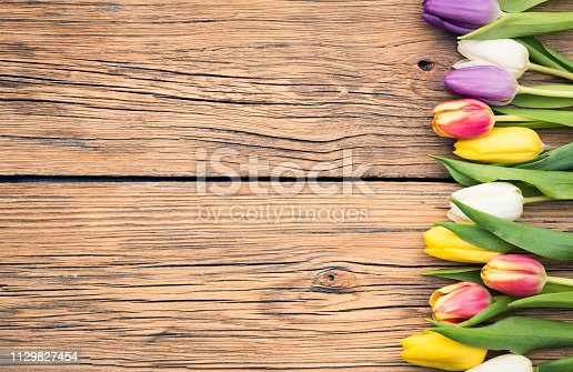 Fresh colorful tulips on a shabby wooden background for Mother's Day. Spring Easter Holiday Concept. Top view, copy space