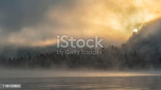 Mountain lake twilight just after sunrise, foggy, strange colors.