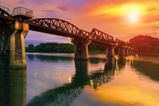 colorful twilight time of river khaw bridge in kanchanaburi most popular world war II history traveling destination in western of thailand colorful twilight time of river khaw bridge in kanchanaburi most popular world war II history traveling destination in western of thailand railway bridge stock pictures, royalty-free photos & images