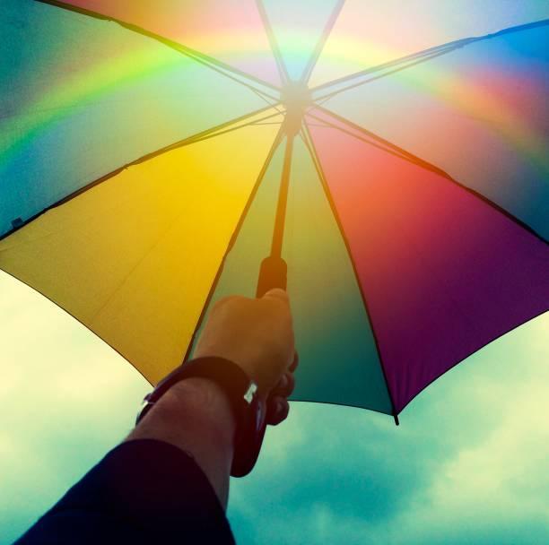 bunten regenschirm in der hand - wettervorhersage deutschland stock-fotos und bilder