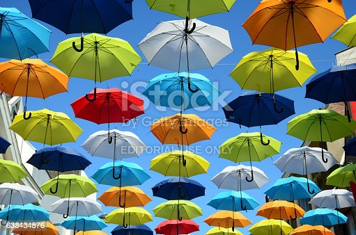 istock Colorful umbrellas background. Colorful umbrellas in the sunny sky. Street decoration. 638434876
