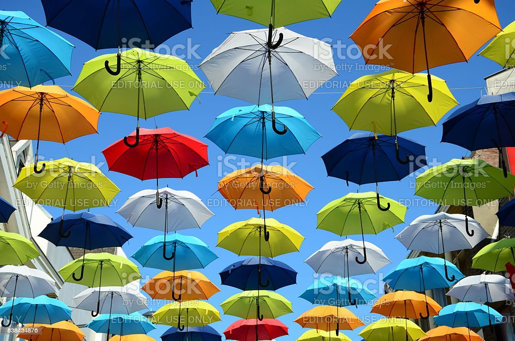 Colorful umbrellas background. Colorful umbrellas in the sunny sky. Street decoration. stock photo