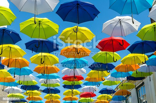 istock Colorful umbrellas background. Colorful umbrellas in the sunny sky. Street decoration. 869889544