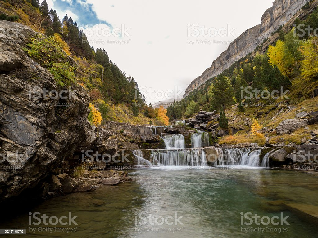 Colorful valley in autumn with a waterfall stock photo