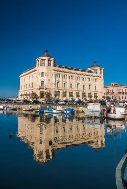eine bunte vielfalt an booten und schiffen füllen die anlegestellen der häfen der insel ortygia, syrakus (siracusa), eine historische stadt auf der insel sizilien, italien. - ortygia stock-fotos und bilder