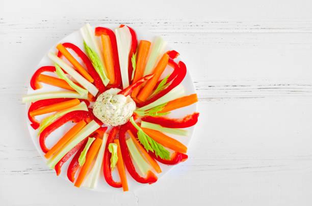 Palitos de vegetais coloridos em um prato com molho de mergulho - foto de acervo
