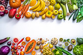Colorful vegetables and fruits vegan food in rainbow colors arrangement leaving copy space isolated on white