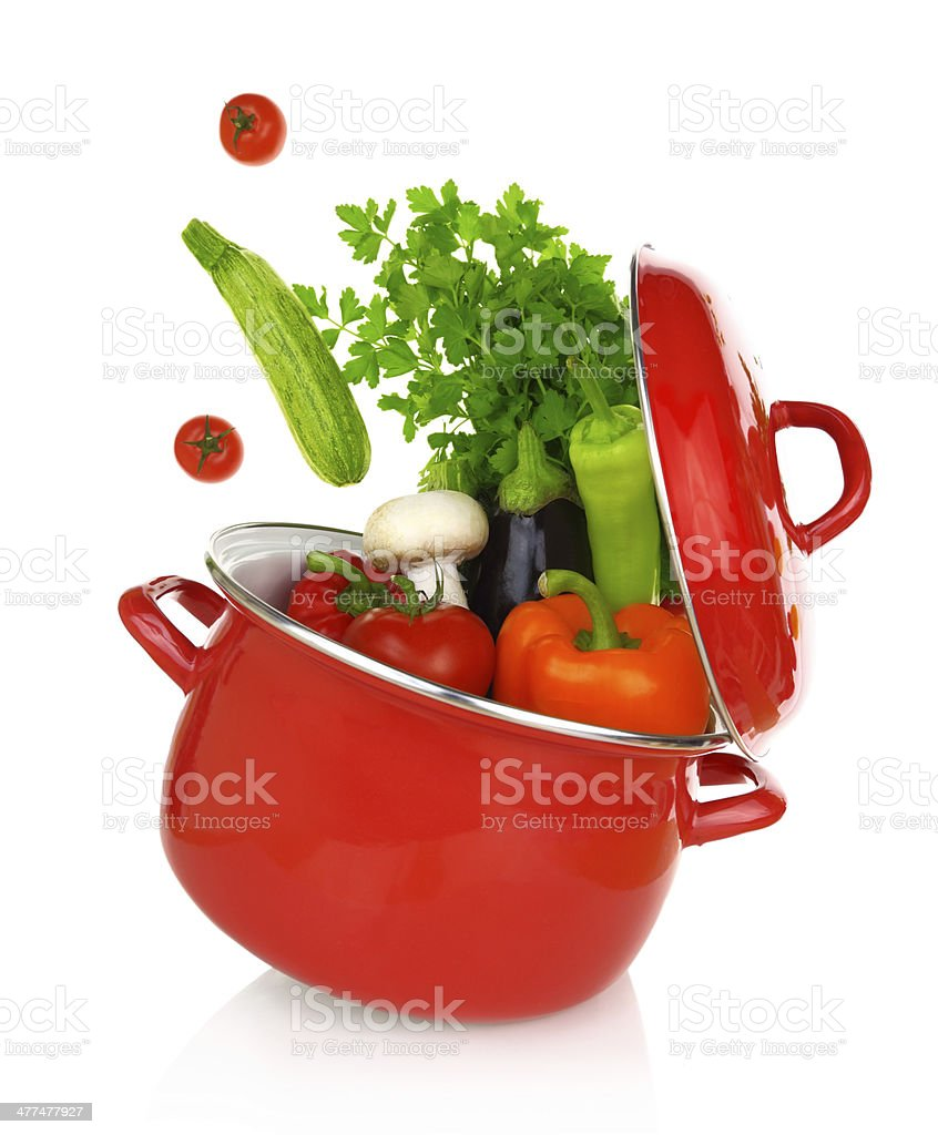 Colorful vegetables coming of a red cooking pot stock photo