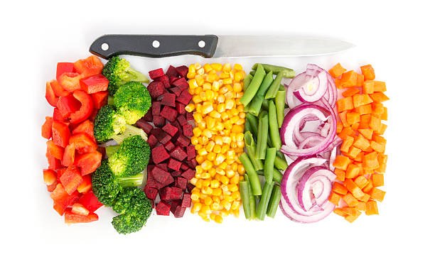 Colorful vegetables Cut colorful vegetables in line with knife on white background chopped food stock pictures, royalty-free photos & images