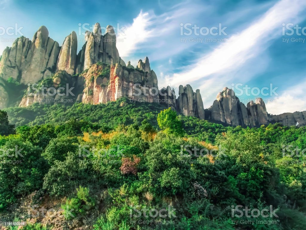 Colorful vibrant landscape of the Montserrat mountains in Catalonia (Spain) Colorful vibrant landscape of the Montserrat mountains in Catalonia (Spain). Beautiful scenery with a bizarre mountain and green and yellow plants on an autumn sunny day At The Bottom Of Stock Photo