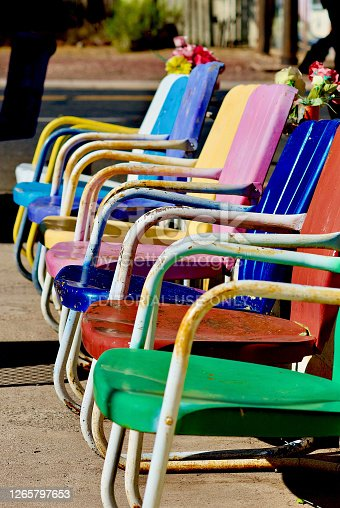 Seligman, Arizona, USA - July 30, 2020: Colorful antique metal chairs at Delgadillo's Snow Cap drive-in await customers, an iconic landmark along historic Route 66 in the heart of Seligman, Arizona.