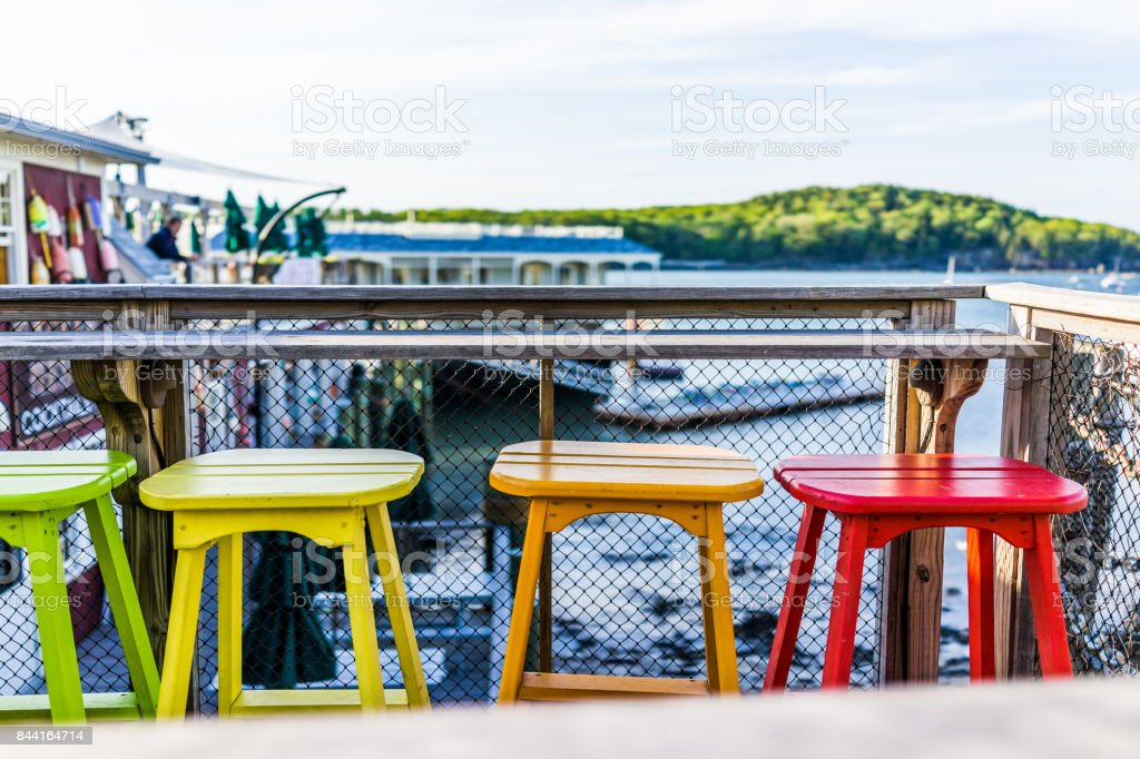 Colorful vivid chairs painted green, yellow and orange on waterfront bar restaurant stock photo