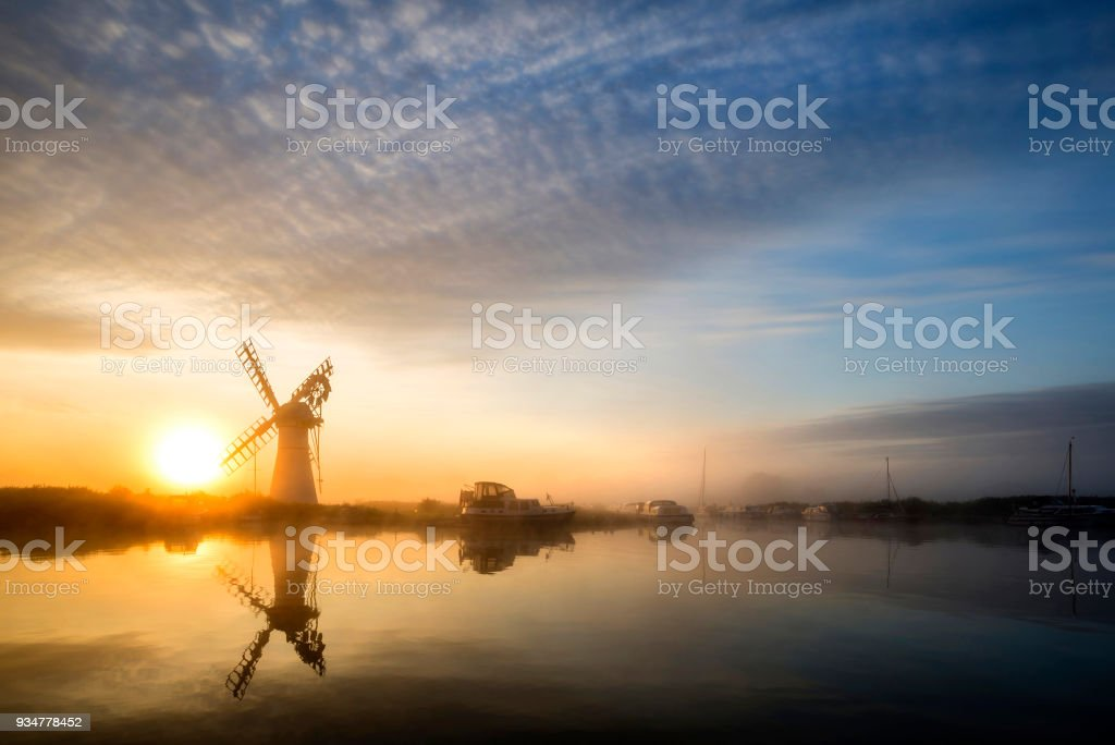 Colorful vunrise landscape over foggy River Thurne looking towards Thurne Mill Windmill stock photo